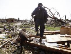 Brent Koeninger, with Oklahoma Task Force One search-and-rescue, and his search dog Huck comb through debris looking for victims Tuesday in Joplin, Mo.