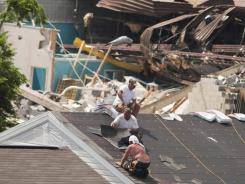 Roofers try to patch up a home Tuesday in Tuscaloosa, Ala.