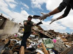 Dave Green, a volunteer from Miami, tosses personal items to Shandie Spencer, who rode out Sunday's tornado in the basement of her destroyed home in Joplin, Mo.