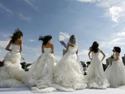 Models present wedding gowns during a show by the M&Y Wedding Design in Beijing on April 23.