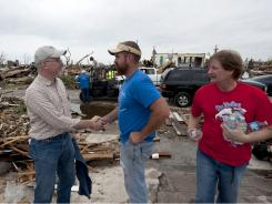 David Vanderhoofven, left, who lost his wife and son in the tornado that ripped through Joplin, Mo., thanks volunteers Jeremiah Moore and Chris Carter, of Freedom Fellowship Church, for bringing food and water.