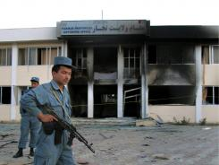 Afghan security stand at the site where a suicide bomber blew himself up inside the provincial governor's compound Saturday in Taloqan, Takhar province, north of Kabul, Afghanistan.