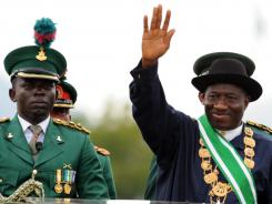 President Goodluck Jonathan stands next to the commander brigade of guards while waving to the crowds after his inauguration in Abuja on on Sunday.