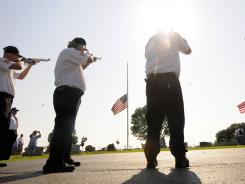 A group of American Legion members from Danville, Ind., Post 118 perform a 21-gun salute to fallen vets on the group's annual Memorial Day tour.