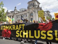 "Crowd holds a banner reading ""stop nuclear power"" in front of the Reichstag Building, housing the German parliament."