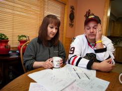 Tina and Chris Hodges of Portage, Ind., look at a stack of medical bills they racked up because of the high deductible on their insurance.