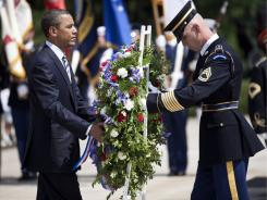 President Obama holds a wreath at the Tomb of the Unknowns at Arlington National Cemetery on Monday.