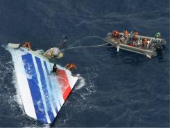 Divers recover part of the tail section from the Air France jet that crashed in midflight over the Atlantic Ocean on June 1, 2009.