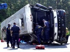 Virginia State Police team inspect a bus that was involved in a single-vehicle accident on Tuesday, killing four people.