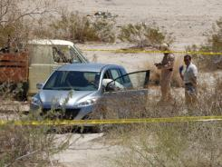 Investigators check a vehicle found 13 miles northwest of Yuma, Ariz., thought to be that of a man suspected of shooting five people in Yuma before taking his own life.