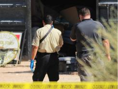 Yuma County Sheriff's detectives investigate the scene of a homicide at a residence Thursday in Wellton, Ariz.