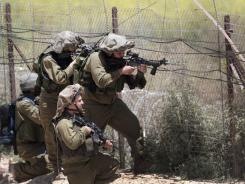 Israeli soldiers keep their position along Israel's border with Syria as demonstrators trying to head into the Israeli-annexed Golan Heights gather on the other side of the fence.