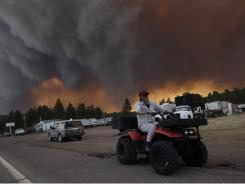 Robert Joseph, 64, rides his ATV as the Wallow Fire dark-ens Luna, N.M., skies Monday, threatening a line of mountain towns.