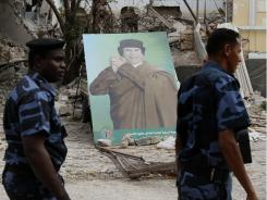 Libyan soldiers walk past  Gadhafi's portrait seen next to a damaged building in Tripoli, Libya on Monday.