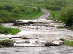 Water washes out a road leading up to a home along Lower Road at Rocky Boy's Indian Reservation, Mont., June 3.