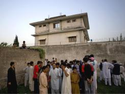 Pakistani residents gather outside the compound where bin Laden was captured.