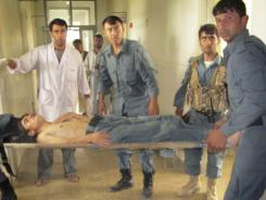 Police officers carry an injured Afghan police officer on a stretcher at a hospital in Kunduz city, in the northern province of Kunduz, Afghanistan on Friday.