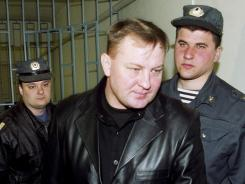 A 2003 photo shows then-Russian army colonel Yuri Budanov passing by policemen in court.
