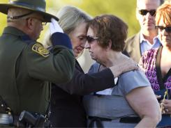 Arizona Gov. Jan Brewer hugs Josephine Terry, mother of Border Agent Brian Terry, during a memorial last month in Phoenix.