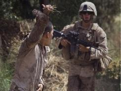 Lance Cpl. Blas Trevino of the 1st Battalion, 5th Marines, left, holds onto the gunshot wound in his belly as he runs to a medevac helicopter in Afghanistan.