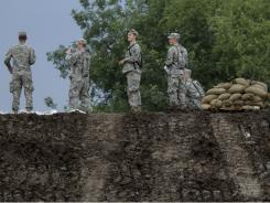 Iowa National Guard members stand on top of a levee that was built to hold back floodwaters from the Missouri River Thursday in Hamburg, Iowa.