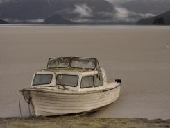 A boat covered by volcanic ash sits docked on the bank of Nahuel Huapi Lake on Thursday in southern Argentina.