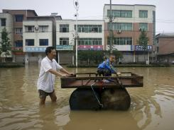 A Chinese man pushes a makeshift drum raft while a child sit on it in a flooded street in Xianing city in central China's Hubei province on Wednesday.