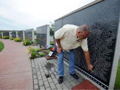 John Bartosiewicz, of Burbank, Ill., and vice president of the Illinois Motorcycle Freedom Run, finds the name of Phillip J. Brodnick on the Middle East Conflicts Wall Memorial in Marseilles, Ill. on Wednesday. Brodnick is the son of a Burbank police officer.
