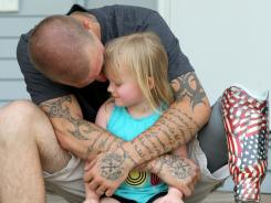 Joel Klobnak, 24, hugs his daughter, Grace, 3, outside his Greenfield, Iowa, home on June 8.