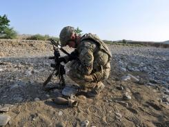 Army Sgt. 1st Class Alex Kenrick examines a mortar round found in a river bed in a village Sunday near an outpost in Afghanistan's eastern Khost province.