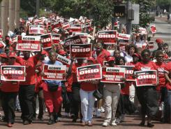 Marchers carry signs in Columbus, Ohio, during a rally for a higher minumum wage organized by ACORN.