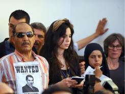 "A man with a poster on his shirt reading ""Wanted for Dictature"" and showing deposed Tunisian president Zine el Abidine ben Ali attends the opening of the trial of Ben Ali and his wife Monday."