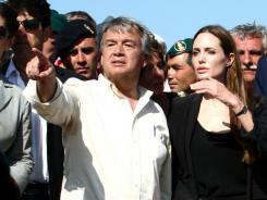 Angelina Jolie listens to United Nations High Commissioner for Refugees Antonio Guterres during a visit to the Italian island of Lampedusa on Sunday. Jolie thanked residents for hosting thousands of refugees who have fled unrest in north Africa in recent months.