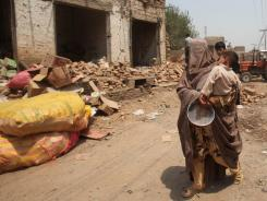 A villager walks past shops damaged on the outskirts of Peshawar, Pakistan.