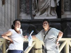 Nelli Bojorquez, left, and Ricardo Amado, from Mexico City, listen to the iPod application guide during their visit inside the St. John in Lateran Basilica, in Rome, Tuesday.