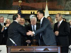 Massachusetts Gov. Mitt Romney, right, shakes hands with Health and Human Services Secretary Timothy Murphy in 2006, after signing a bill designed to guarantee health insurance to nearly all state residents.