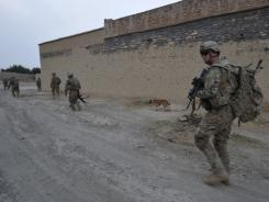U.S. soldiers walk through a village in eastern Afghanistan on Wednesday. Marines take cover during a firefight with militants in Helmand province in October 2009.