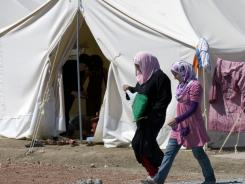 Syrian refugees walk in a newly opened camp in the Turkish town of Yayladagi in Hatay province, Turkey. The U.N. refugee agency said  that 500 to 1,000 people a day have been crossing from northern Syria into Turkey since June 7.