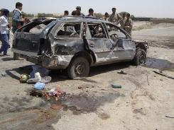 Afghan security forces stand at the site of a suicide car bomb attack in Kunduz on Sunday. Three Afghan civilians were killed and 11 wounded when a suicide car bomber targeted a passing foreign forces convoy in Kunduz.