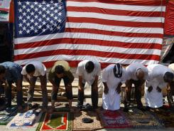 Anti-Gadhafi protesters pray during Friday prayers in front of a U.S. flag at the court square, in Benghazi, Libya.