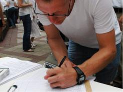 Brian May, of Birmingham, signs a petition against Alabama's new law cracking down on illegal immigration.