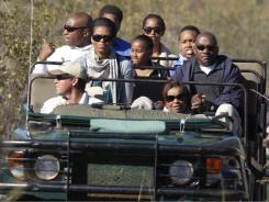 First lady Michelle Obama and her family ride their safari vehicle in Madikwe Game Reserve in South Africa.