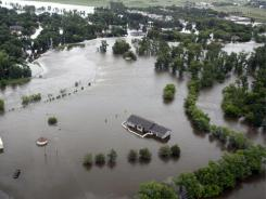 In this aerial photo flood waters from the Souris River surround a house near Burlington, N.D., Friday, June 24.