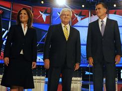 Republican candidates Michele Bachmann and Mitt Romney stand with fellow candidate Newt Gingrich, center, at a debate in New Hampshire.