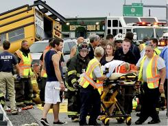 A child is taken to an ambulance after a bus and automobile were involved in a crash on Interstate 81 in Chambersburg, Pa.