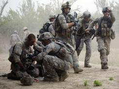 In Kandahar: Army troops help each other after a blast of an improvised mine.