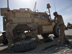 Marines repair an MRAP vehicle at Forward Operating Base Payne in April.
