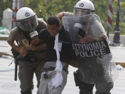 A protester is arrested by police during a demonstration in Athens on Tuesday.