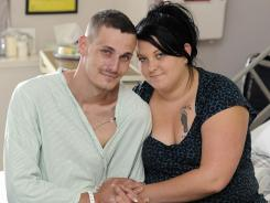 Derek McBride, and Cassy McBride pose for a photo in Derek's hospital room Monday.