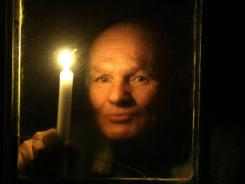 Photo from 2005 shows a man holding a candle in front of the window of his house in the village of Konotop, Belarus.  Russia  cut power supplies to cash-strapped Belarus on Wednesday.